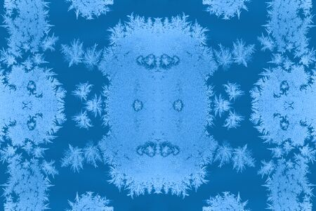 Fantastic unusual pattern of repeated frosty patterns. Trendy toning in color 2020 Classic Blue. Christmas festive natural background. Collage, selective focus.