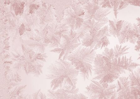 Christmas or New year abstract background or wallpapers. Defocused beautiful winter frosty pattern on window glass toned in pink. Stockfoto