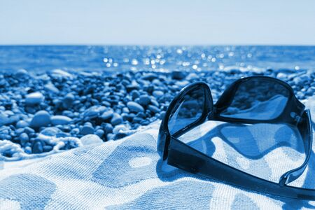 Close-up sunglasses on beach towel on pebbly sea beach. Trendy toning in color 2020 Classic Blue. Vacation concept in trendy color. Selective focus, copy space. Stockfoto