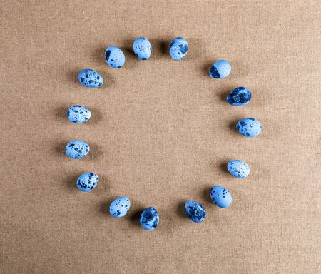 Set of spotted quail eggs, colored in trendy color of 2020 Classic Blue, lying in circle on rough rustic canvas.