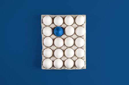 Cardboard quadratic box with white eggs and one blue painted Easter egg on trendy background 2020 Classic Blue.