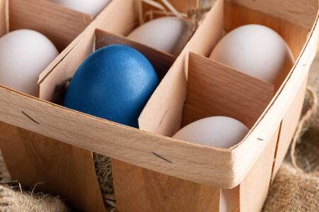 Close-up eco-friendly wooden box with white eggs and one blue Easter egg.