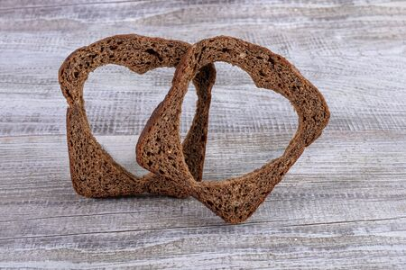 Two rye bread slices with carved holes of heart shape in them on old wooden grey table. Healthy leavened bread. Valentines or mothers day concept. Copy space, selective focus.