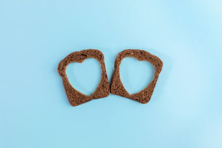 Two rye bread slices with carved holes of heart shape in them on light blue background. Creative minimal concept.