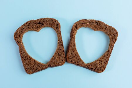 Two rye bread slices with carved holes of heart shape in them on light blue background. Top view, close-up.