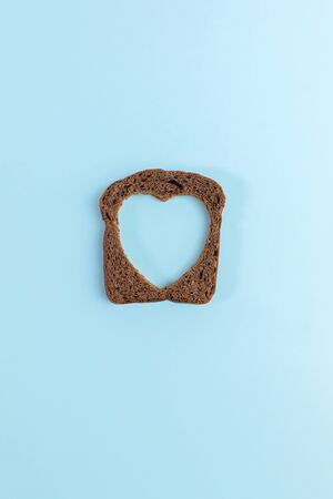 One rye bread slice with carved hole of heart shape in it on light blue background. Creative minimal concept.