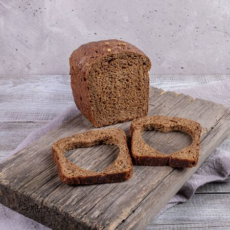 Loaf of rye bread and two slices with carved holes of heart shape in them on old wooden Board on grey background. Healthy leavened bread. Valentines or mothers day concept. Selective focus. Stockfoto