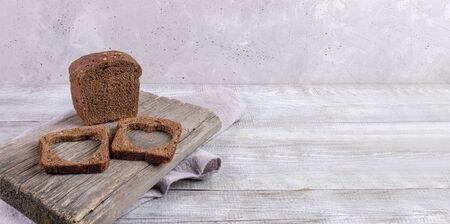 Loaf of rye bread and two slices with carved holes of heart shape in them on old wooden Board on grey background. Valentines or mothers day concept. Banner, copy space for text, selective focus.