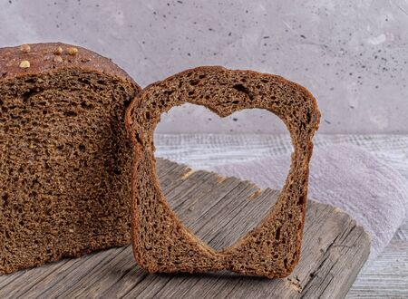 Loaf of rye bread and slice with carved hole of heart shape in it on old wooden board on grey concrete backdrop.