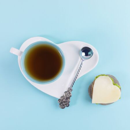 Cup of tea and silver spoon on saucer in heart shape and sandwich with cheese and herbs in heart shape on light blue background.