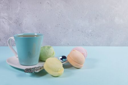 Blue cup of tea and silver spoon on white saucer and colorful sweet zephyrs on light blue table on concrete background.