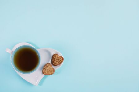 Blue cup of tea and sweet cookies as heart on saucer in heart shape on light blue background. Valentines day concept. Stockfoto