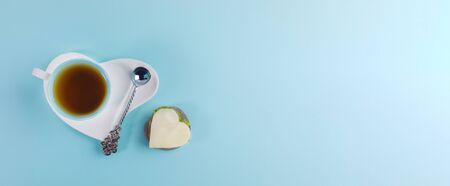 Cup of tea and silver spoon on white saucer in heart shape and sandwich in heart shape on light blue background. Banner.