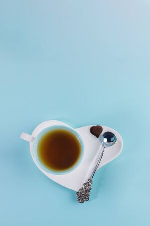 Blue cup of tea with silver spoon and one chocolate candy on white saucer in heart shape on light blue background. Romantic breakfast. Valentines day or mothers day concept. Top view, vertical orientation.