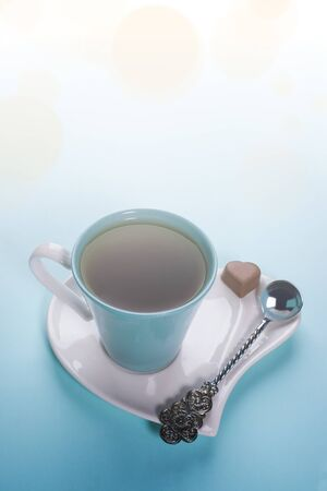 Romantic breakfast or Valentines day or mothers day concept with cup of tea with silver spoon and chocolate candy on saucer in heart shape on light blue background. Vertical orientation.
