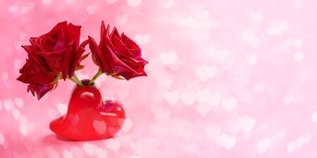 Close-up three red roses in red vase shaped heart on pink bokeh background with hearts. Valentines day or mothers day festive banner. Copy space for text.