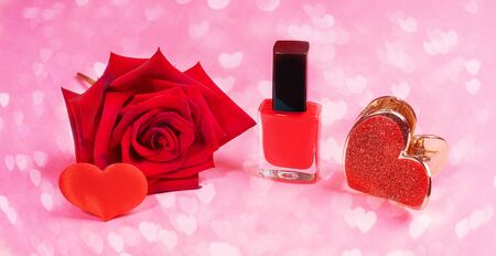 Close up all red: nail polish, hair clip, rose and small heart on pink background with bokeh with hearts. Valentines day, mothers day or Womens day. Womens beauty and care concept.