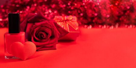 Red festive Valentines day or mothers day banner. Nail polish, textile heart, rose, gift box on red background with bokeh. Womens beauty and care concept. Copy space for text.