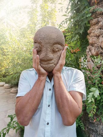 Male in light blue shirt holding in hands stone carved mask instead of face in green tropical garden. Man without face. Creative trendy image. Faceless man.
