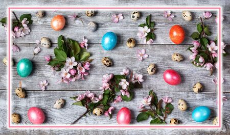 Easter festive layout of pink Apple tree twigs, quail and colored hen eggs on wooden table with rectangular pink glowing frame above. Easter decorations composition. Top view, flat lay. Reklamní fotografie
