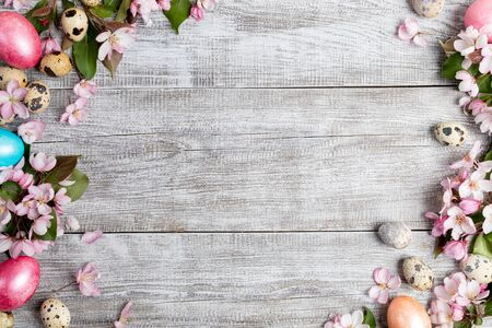 Festive Easter mockup. Frame of pink Apple tree flowers, quail eggs, colored Easter hen eggs on painted grey wooden background. Top view, flat lay, copy space.