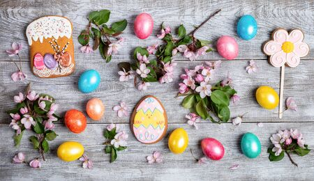 Easter festive layout of pink Apple tree twigs, quail and colored hen eggs, gingerbreads as if Easter cake, flower and funny egg on wooden table. Easter decorations composition. Top view, flat lay.