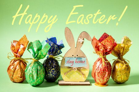 Wrapped in colored paper Easter eggs and wooden figure bunny in mask with words stay home are standing on neo mint backdrop. Words Happy Easter. Pandemic Covid-2019. Easter 2020 during quarantine. Banque d'images