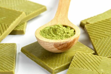 Close-up wooden spoon of japanese matcha tea powder and set of square slices of green chocolate with matcha on white. Matcha chocolate is healthy dessert rich with antioxidants. Selective focus.