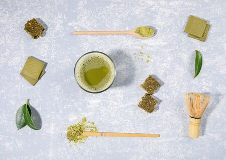 Flat lay arrangement of matcha tea glass, wooden spoons with matcha powder, whisk, leaves, chocolate, granola bar on light grey textured background. Knolling layout. Top view. 写真素材