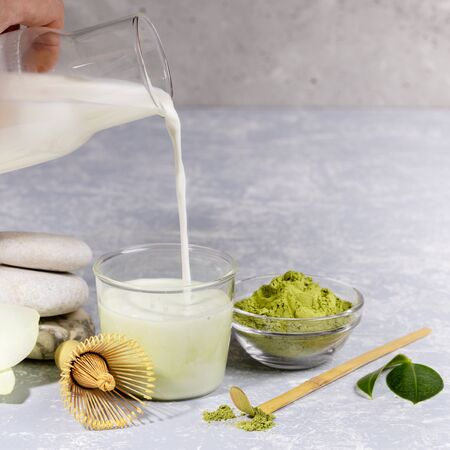 Preparation of matcha tea latte. Milk is pouring from a bottle into a glass with powder. Ingredients and accessories for making matcha tea. Matcha tea is source of antioxidants. Copy space for text.