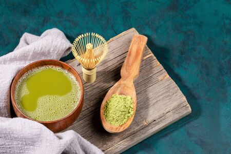 Wooden cup of japanese green matcha tea, matcha powder in wooden spoon, bamboo whisk for whipping on old wooden board on emerald backdrop. Matcha tea is organic drink rich of antioxidants. Copy space.