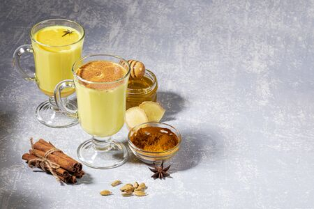 Organic ayurvedic turmeric milk for immunity. Two glasses for mulled wine with golden milk with ingredients on light grey background. Healthy eating, diet and detox. Copy space, selective focus.