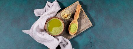 Wide banner with of asian green matcha tea, powder and bamboo whisk for whipping on old wooden board on emerald backdrop. Matcha tea is organic drink rich with antioxidants. Top view, copy space.