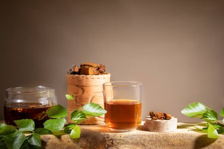 Healing beverage from birch mushroom chaga, chaga mushroom pieces, twigs on wooden plank on beige backdrop. Chaga coffee or tea. Strong antioxidant improving immunity. Superfood drink. Copy space.
