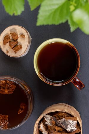 Healing beverage of birch mushroom chaga in ceramic cup, mushroom pieces on black backdrop. Chaga tea or coffee. Trendy healthy beverage, superfood improving immunity. Top view, vertical orientation.