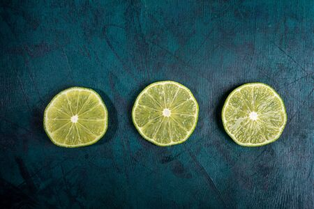 Three ripe fresh juicy cut lime slices are laid out in row on emerald green background. Lime is ingredient for refreshing Mojito drink. Top view, copy space.
