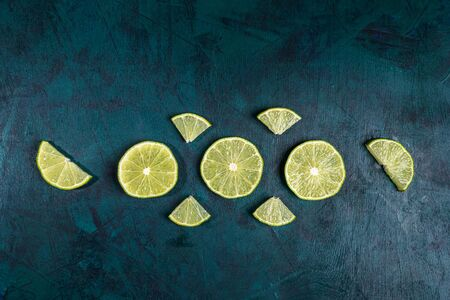 Set of ripe fresh juicy differently cut lime slices are laid out on emerald green background. Lime is ingredient for refreshing Mojito drink. Top view, flat lay, copy space. Standard-Bild