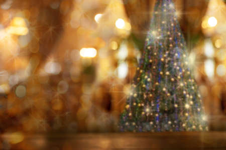 Abstract Christmas blurred bokeh background with rustic wood table in front of Christmas tree. Copy space for text. Stay at home in feast day. Christmas at home. 免版税图像
