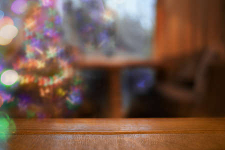 Cozy Christmas blurred background with bokeh, wooden table, Christmas tree in living room and wooden tabletop in foreground. Copy space for text. Stay at home in festive day. Xmas at home.