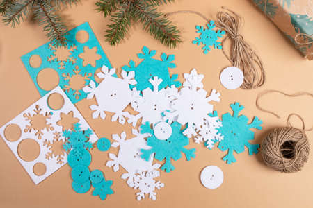 DIY instruction. Step by step tutorial. Making Xmas toy snowflake of felt. Step 4 - Spread out all ready details of snowflakes on table. Top view, flat lay.