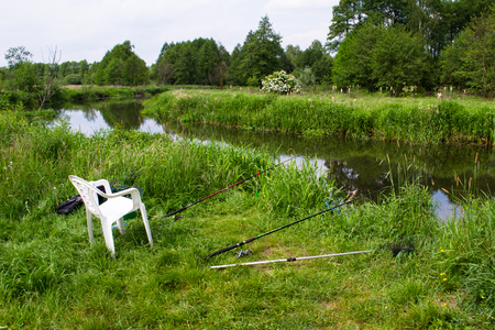 scrub grass: Fishing rods on the river.
