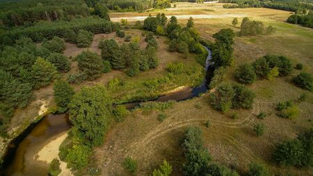 A small river in central Poland, flowing among green meadows and forests. Фото со стока