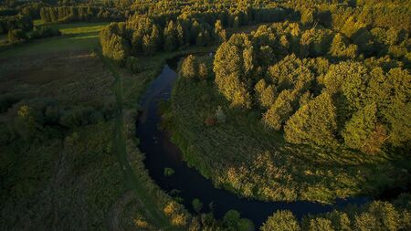 Small river in central Poland, flowing among green meadows and forests.