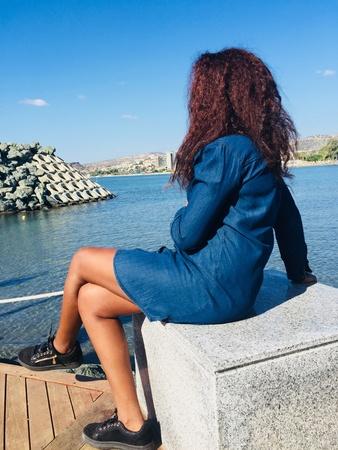 Girl sitting on stone beside sea
