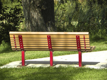 rearview: Clean tan and red slatted park bench, rearview