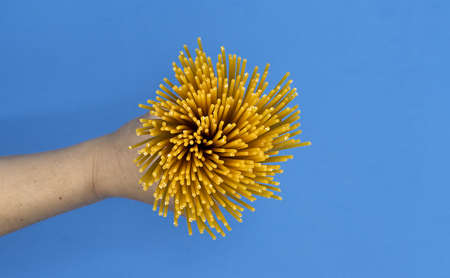 A hand with spaghetti on blue background, top view