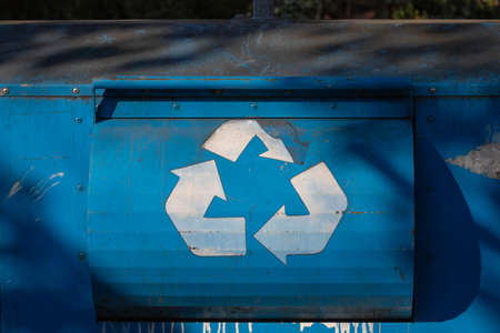 white recycling sign on the blue recycle bin. deformed recycling sign. used recycling bin.