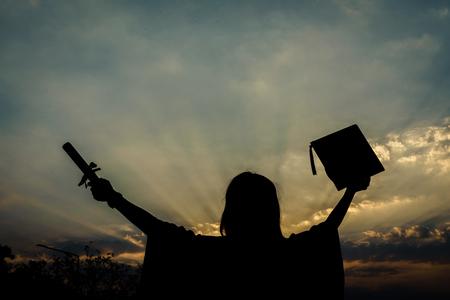 女大学毕业生兴高采烈地庆祝毕业典礼并获得学位证书。