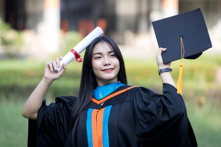 Portrait of happy and excited of young Asian female university graduate wears graduation gown and hat celebrates with degree in university campus in the commencement day. Education concept.