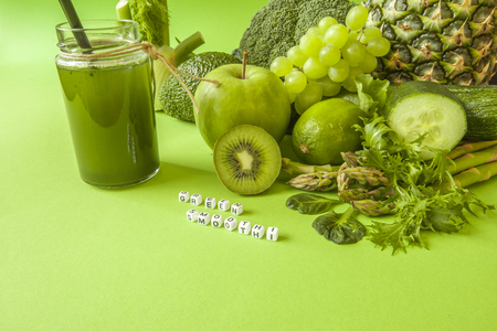 Green health smoothie fruits and vegetables, kale leaves, lime, apple, kiwi, grapes, banana, avocado, lettuce pineapple salat. Copy space. Raw, vegan, vegetarian, alkaline food concept.
